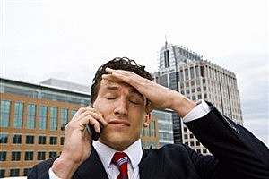 Man on cell phone with a headache