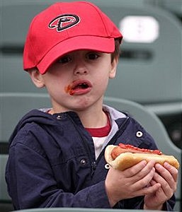 Little boy eating a hot dog
