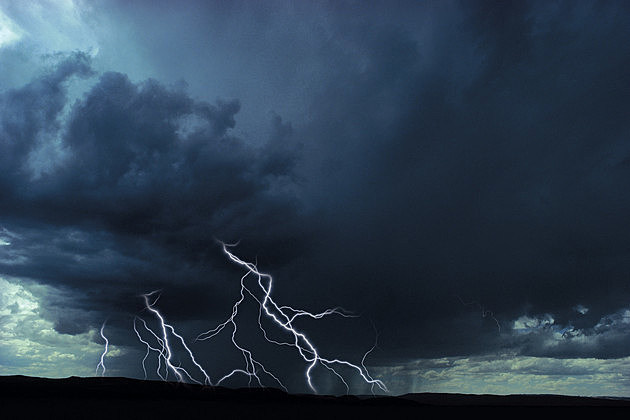 Multiple lightning bolts over rural landscape. ThinkStock