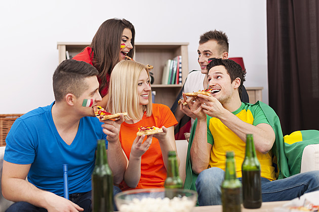 Multinational people eating pizza during the break in football match